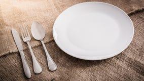 Leeren Sie weiße Platte und Löffel, Gabel, Messer Stockfotos
