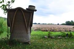 Leerer alter Stuhl steht mit Blick auf das Feld lizenzfreies stockbild