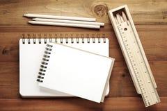 Leerer Anmerkungsbuch-, Bleistift-, Machthaber- und Bleistiftkasten auf hölzernem backgrou Lizenzfreie Stockfotografie