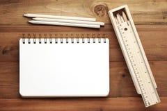 Leerer Anmerkungsbuch-, Bleistift-, Machthaber- und Bleistiftkasten auf hölzernem backgroun Stockfotos