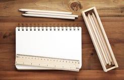 Leerer Anmerkungsbuch-, Bleistift-, Machthaber- und Bleistiftkasten auf hölzernem backgroun Lizenzfreie Stockfotos