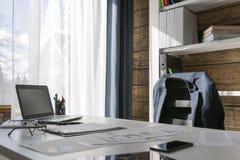 Leerer Arbeitsplatz mit Schreibtisch und Stuhl, Jacke auf dem Stuhl, stockfotografie