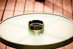 Leerer Aschenbecher steht mitten in einem runden Glastisch Stockfotografie