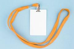 Leerer Ausweis/Ikone mit einem orange Gurt, auf einem blauen Hintergrund Stockfoto