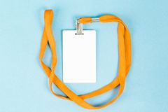 Leerer Ausweis/Ikone mit einem orange Gurt, auf einem blauen Hintergrund Stockfotografie