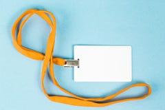 Leerer Ausweis/Ikone mit einem orange Gurt, auf einem blauen Hintergrund Lizenzfreies Stockbild