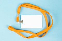 Leerer Ausweis/Ikone mit einem orange Gurt, auf einem blauen Hintergrund Stockbild