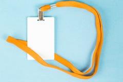 Leerer Ausweis/Ikone mit einem orange Gurt, auf einem blauen Hintergrund Lizenzfreie Stockfotografie