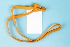 Leerer Ausweis/Ikone mit einem orange Gurt, auf einem blauen Hintergrund Stockfotos