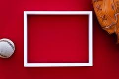 Leerer Bilderrahmen auf einer roten Wand mit Baseballausrüstung Lizenzfreies Stockbild
