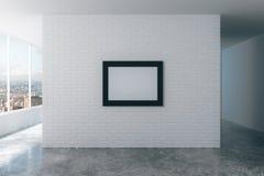 Leerer Bilderrahmen auf weißer Backsteinmauer im leeren Dachbodenraum, Spott Lizenzfreies Stockbild