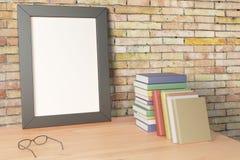 Leerer Bilderrahmen, der auf einem Holztisch mit Büchern steht lizenzfreie abbildung