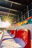 Leerer bunter Fußball ( Soccer) Stadions-Sitze im Winter umfasst im Schnee - Sunny Winter Day mit Sun-Aufflackern stockfoto