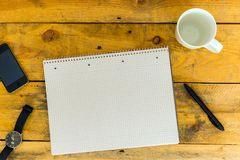 Leerer College-Schreibens-Block, Stift, leere Kaffeetasse, Armbanduhr und Handy auf rustikalem Holztisch, Draufsicht Stockbild