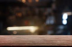 Leerer dunkler Holztisch vor abstraktem unscharfem Hintergrund des Restaurant-, Café- und Kaffeestubeinnenraums kann für verwende lizenzfreies stockfoto