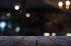 Leerer dunkler Holztisch vor Zusammenfassung verwischte Hintergrund des Café- und Kaffeestubeinnenraums Kann für Anzeige verwende stockfoto