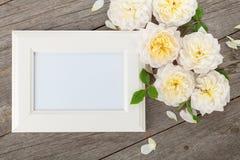 Leerer Fotorahmen und weiße Rosen Stockfotos