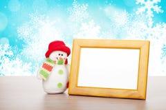 Leerer Fotorahmen und Weihnachtsschneemann auf Holztisch Stockfotos