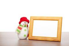Leerer Fotorahmen und Weihnachtsschneemann auf Holztisch Lizenzfreies Stockbild