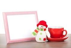 Leerer Fotorahmen, Weihnachtsschneemann und Kaffeetasse auf hölzernem ta Lizenzfreie Stockfotografie