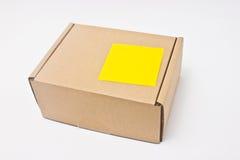Leerer gelber klebriger Anmerkungsbeitrag auf Papierkasten. Stockfoto