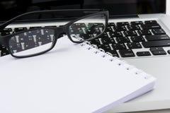 Leerer Geschäftslaptop, -maus, -stift, -gläser und -anmerkung Stockfotografie