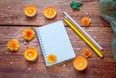 Leerer gewundener Notizblock, bunte Bleistifte und brennende Aromakerzen Lizenzfreie Stockbilder