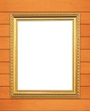 Leerer goldener Rahmen auf hölzerner Wand Stockbilder