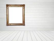 Leerer goldener Rahmen im Raum mit weißer hölzerner Wand und Holzfußboden stockfotografie