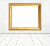 Leerer goldener Rahmen im Raum mit weißer hölzerner Wand und Holzfußboden lizenzfreie stockfotos