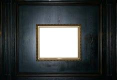Leerer Goldrahmen auf einem schwarzen hölzernen Hintergrundkopienraum stockfoto