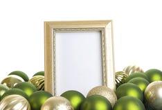 Leerer Goldrahmen mit Weihnachtsverzierungen auf einem weißen Hintergrund Stockbilder