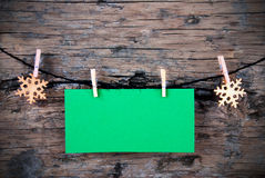 Leerer grüner Aufkleber mit Schneeflocken auf einer Linie auf Holz Lizenzfreies Stockbild