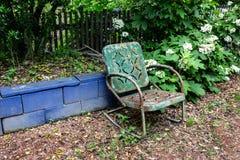 Leerer grüner Metallstuhl gegen eine blaue Blockwand, alterndes Todesleid-Abwesenheitskonzept Lizenzfreie Stockfotos