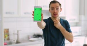 Leerer grüner Schirm der Mannvertretung des intelligenten Telefons zu Hause mit Überraschung stock video