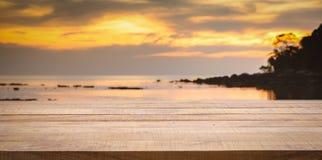 Leerer hölzerner Barzähler mit unscharfem Sonnenuntergangstrandhintergrund stockfotografie