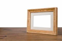 Leerer hölzerner Bilderrahmen auf Tabelle über weißem Hintergrund Stockbilder