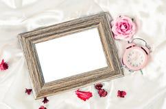 Leerer hölzerner Fotorahmen und rosa Wecker mit stiegen Stockfoto