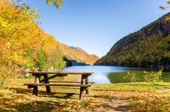 Leerer hölzerner Picknicktisch nahe dem Ufer von einem Mountainsee Stockfotos