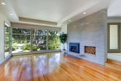 Leerer Hausinnenraum Wohnzimmer mit Glaswand und Backsteinmauer stockfoto