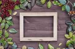 Leerer Holzrahmen auf einer braunen Oberfläche unter den Blättern Stockfotografie