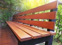 Leerer Holzstuhl oder alte hölzerne Bank im Garten Stockfotografie