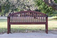 Leerer Holzstuhl oder alte hölzerne Bank im Garten Lizenzfreies Stockfoto