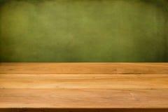 Leerer Holztisch über Schmutzgrünhintergrund. Stockbild