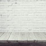 Leerer Holztisch über weißem Backsteinmauerhintergrund Stockfoto
