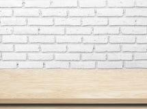 Leerer Holztisch über weißer Backsteinmauer Lizenzfreies Stockfoto