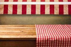 Leerer Holztisch bedeckt mit Rot überprüfter Tischdecke Hintergrund für Produktmontage Stockfotografie