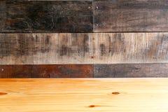 Leerer Holztisch mit dunkler hölzerner Wand, kann als Hintergrund benutzt werden Stockbilder