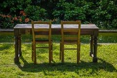 Leerer Holztisch mit Garten und zwei Stühle für Nahrung. Im Freien lizenzfreie stockfotografie