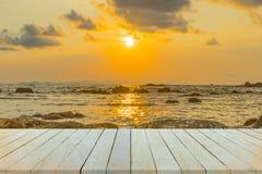 Leerer Holztisch oder Regalwand mit Sonnenuntergang oder Sonnenaufgang auf Sand Lizenzfreie Stockbilder